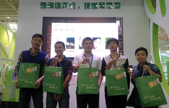 图为森林旅游节海南馆内 获得微信抽奖互动观众上台领奖
