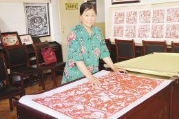 图为郭润芝正在讲解剪纸作品中的抗战故事