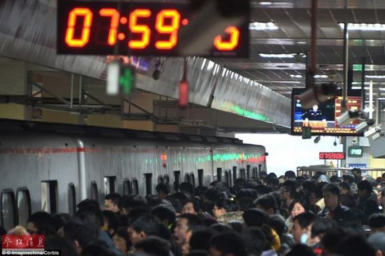 在北京地铁里,人们正在排队等待车门开启。2013年,在北京上下班的旅程平均为11英里(约17702米)。