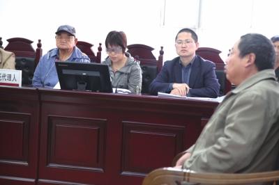 李福(左一)在法庭上听着护工王先生出庭作证。