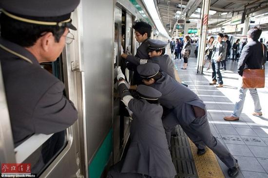 在高峰期,经常需要好几个工作人员才能勉强把火车门关上,乘客也要忍受可怕的乘车环境。