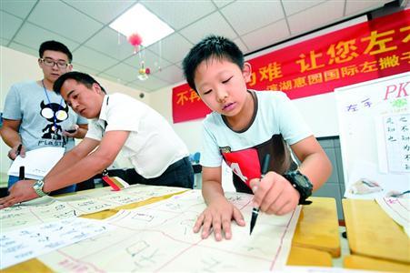 """启发孩子均衡使用左右手是改变左手写汉字别扭的一个好方法。图为8月13日,安徽合肥的一小朋友在参加""""左手写字""""才艺秀。"""