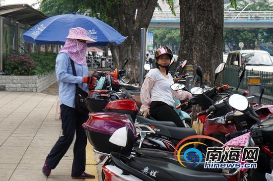 海口街头免费电动车停车位形同虚,图为一中年女子发卡收费。(南海网记者陈丽娜摄)
