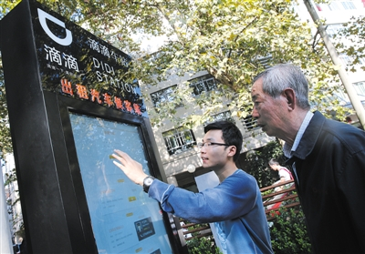 """10月15日,滴滴工作人员(左)指导乘客使用""""滴滴车站""""的电子屏预约出租车。10月14日起,上海首批""""滴滴车站""""上线启用。新华社记者 裴鑫 摄"""