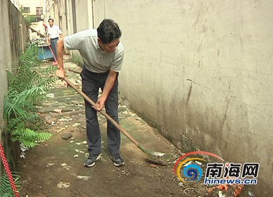 海南省政协主席于迅在永春花园进行清扫(南海网记者陈元能摄)