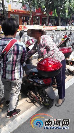 在解放西路一处电动车停放处,一位妇女正在给停车市民发存车卡。