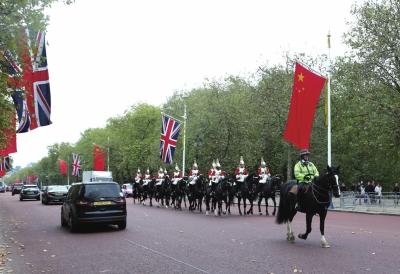 10月17日,在英国伦敦,一队骑兵从悬挂着中、英两国国旗的林荫路上经过。新华社发