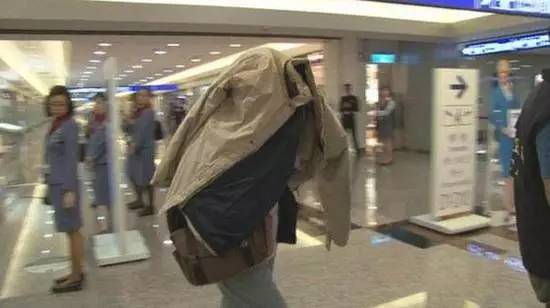 在华航班机上产下女婴的台湾女子已返台,她下飞机后,用夹克盖住自己的身体。