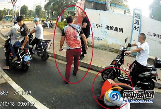 18日的执法现场,乘车人躺在地上,花衣车主正追打便衣交警。(南国都市报记者 田春宇摄)