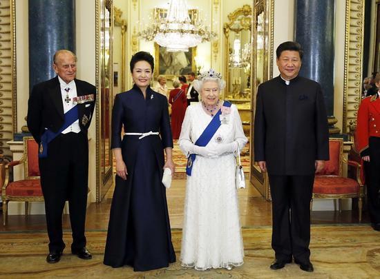 10月20日,国家主席习近平和夫人彭丽媛在伦敦白金汉宫出席英国女王伊丽莎白二世举行的欢迎晚宴。新华社记者 鞠鹏 摄