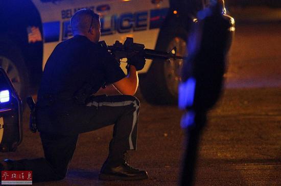 资料图:一名美国警察用枪指着趴在地上的男子。