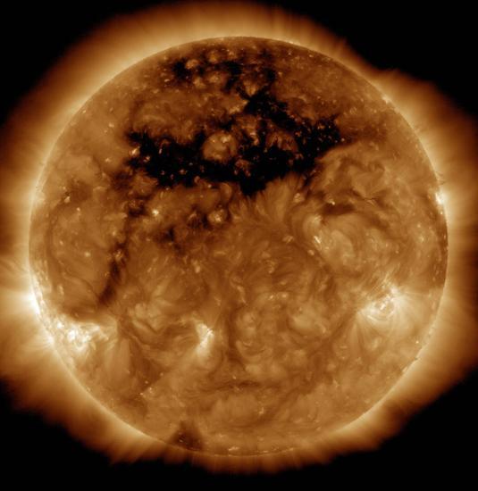 这张图像拍摄于 2015年10月10日, 上部的暗色区域就是一个巨大的冕洞。高速太阳风从这里出发,轰击地球南北极上空大气,从而产生绚丽的极光现象