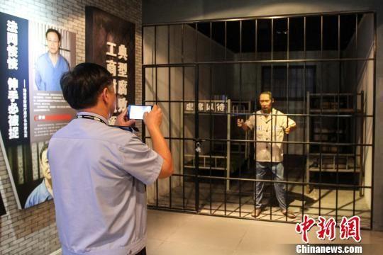 """图为一名参观者拍摄警示教育基地内的""""牢房""""。 洪坚鹏 摄"""