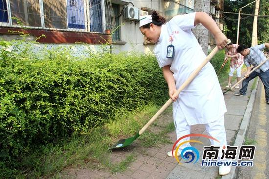 海南省人民医院组织120余名党员,对宿舍小区的卫生死角进行清理。(南海网记者陈望摄)