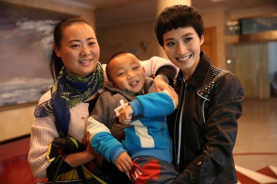 中国儿童少年基金会启智基金公益大使冯文娟到现场看望脑瘫儿童,右一:冯文娟