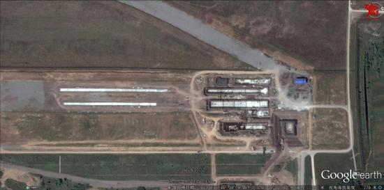 近日曝光在网络上的一张卫星照片显示,国内某地出现两条跑道和相关实验设施,可以看到地面上有类似轨道的凹槽,有观点认为这是正在研制的新型航母弹射装置,而且更有可能是电磁弹射装置。