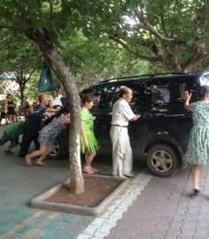 今年夏天坝坝舞成员将一辆小车推向公路。(图据网络)