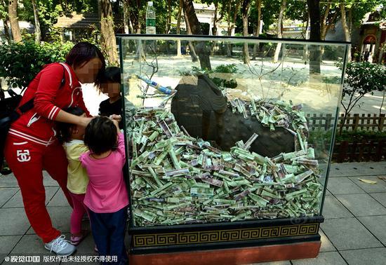 祖庙博物馆,铜像四周堆积成山的钱币。