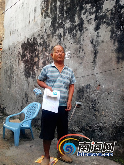 70多岁的残疾老人王德福站在35年的老屋前维权 (南海网记者刘培远摄)