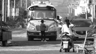 一女子站在校车前不让走