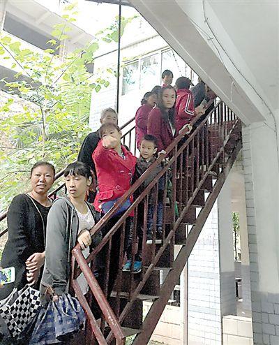 孩子和家长们被疏散到门外的楼梯上