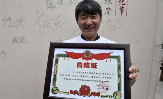 """甘肃游客赵先生以1分钟吃43碗的成绩摘得冠军,还赢得了一张""""白吃证""""。"""