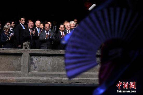 图为重庆市长黄奇帆陪同法国总 统奥朗德观看川剧变脸。 中新社记者 陈超 摄