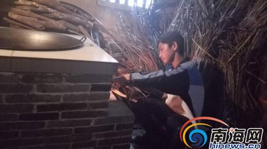 12岁男孩史才锦在厨房生火做饭。南国都市报记者杨琼文摄