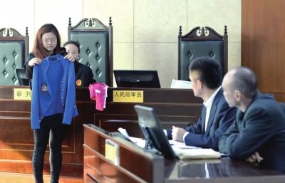 小黎在法庭上展示母亲生前在歌厅的工作服。京华时报记者蒲东峰摄