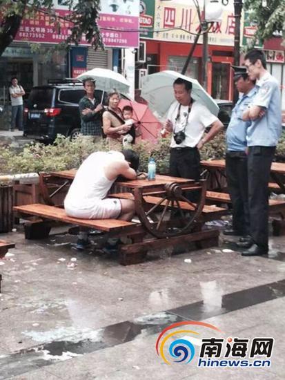 男子趴在路边的桌上,一动不动。 (网友提供)
