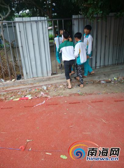 正在铺设塑胶跑道的施工现场有学生进出。
