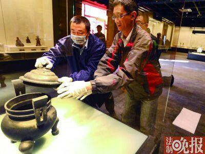 工作人员将清双天官帽耳带盖蹄足铜炉放置在展台上