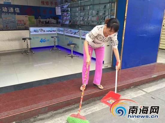 道客路沿街商铺一店员正在打扫门前卫生。