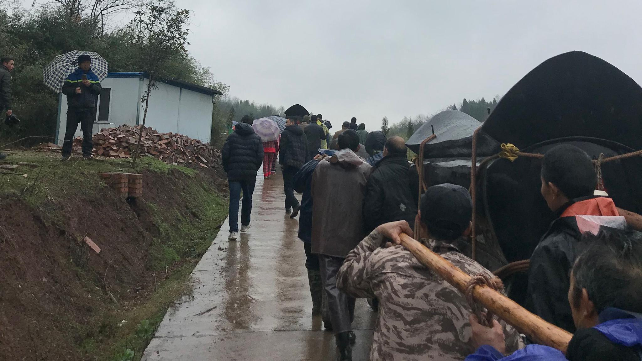 上午8时40分许,被儿子锤杀的罗某夫妇,被亲友们送至家对面的山坡上,入土为安。新京报记者段睿超摄