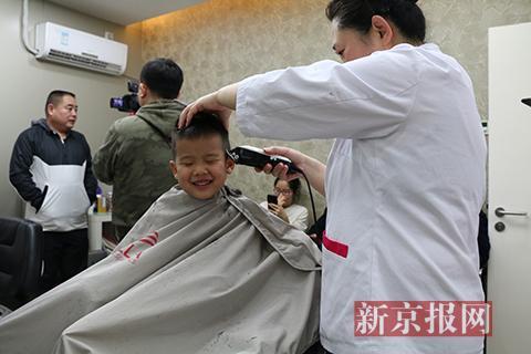 王府井四联理发店内,理发师为市民理发。