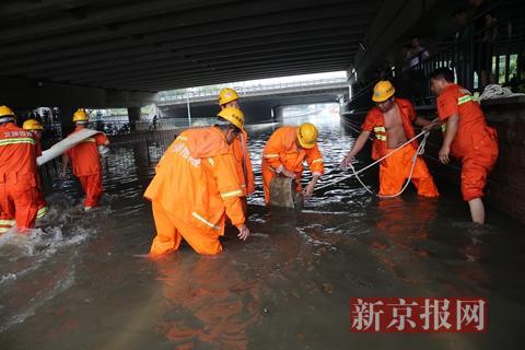 回龙观育知东路城铁桥下抢险救援人员在安装排水泵。新京报记者 王贵彬 摄
