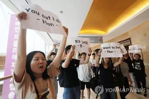 22日,动物保护人士在炸鸡鉴别师大会会场外抗议(图:韩联社)