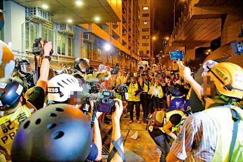 """暴动举动时期,很多身脱反光黄间背心的""""记者""""围着警圆拍摄(图源:至公报)"""