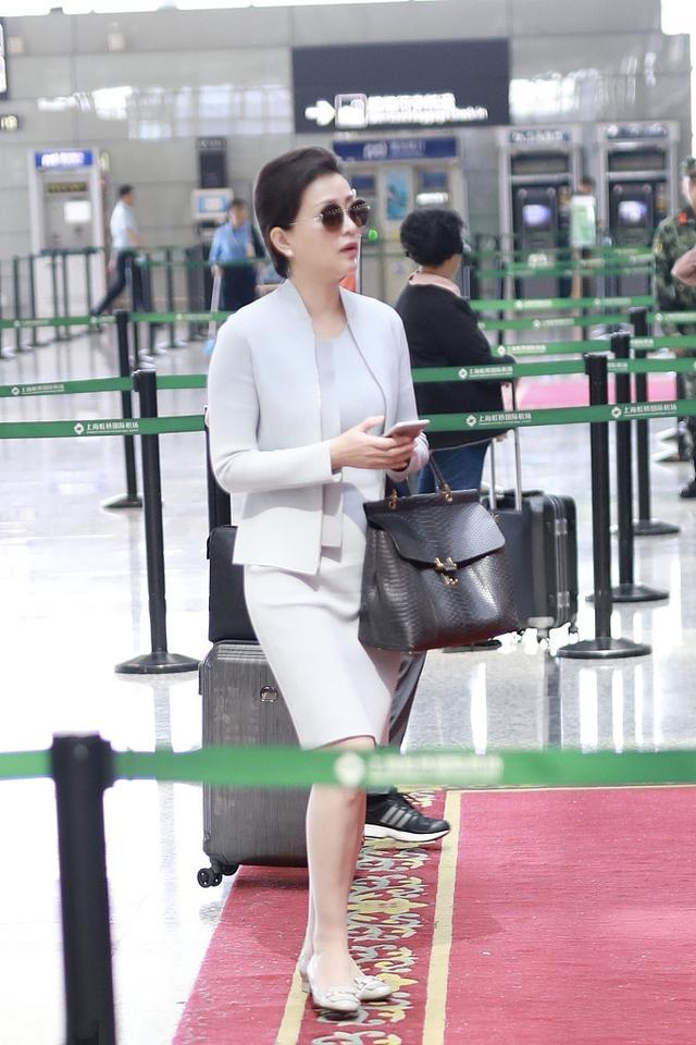 主持人杨澜51岁了,穿西裙套装走机场气质出众,可惜双下巴显老态