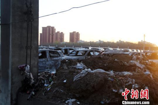 失火现场的垃圾堆和汽车。 赵庆斌 摄
