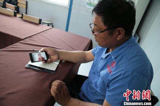 图为张跃强与女儿进行手机视频通话。 张远 摄