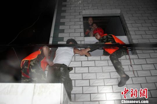 """消防官兵搭""""人梯""""救出被困人员 周刚 摄"""
