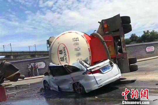 一辆水泥罐车侧翻将一辆小车压扁。通讯员供图