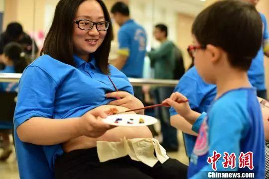 """资料图: 重庆""""二孩家庭,孩子在妈妈肚皮上作画  钟欣 摄"""