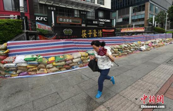一名市民從市區五四路上一商家築起的防禦圍牆前頂風前行。劉可耕 攝