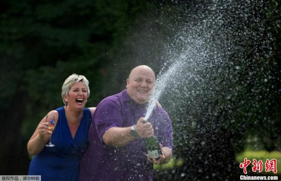 """資料圖:當地時間2012年8月14日,英國哈特菲爾德希斯,""""歐洲百萬樂透""""彩票開出鉅獎,一對英國夫婦中了1.9億歐元(約1.49億英鎊)的彩票獎。圖爲中獎夫婦中獎後慶祝。"""
