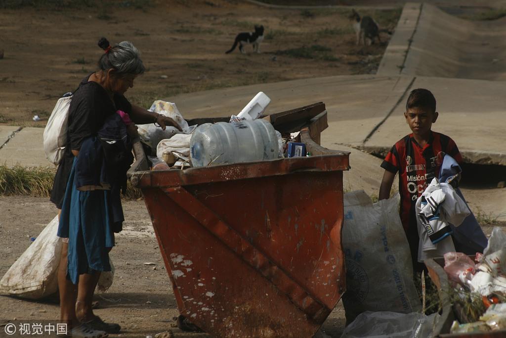 2018年6月7日,委内瑞拉苏利亚州圣弗朗西斯科市,民众在垃圾堆中翻找食物。图自视觉中国