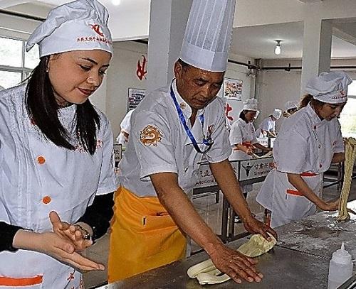 """搭上""""一带一路""""顺风车,兰州拉面想成为""""全球第一快餐""""。图为一名留学生在学习兰州拉面制作方法。(日本《朝日新闻》网站)"""