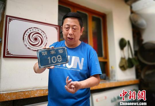 """图为彭维国讲述他收藏的门牌号背后""""消失的村庄""""。 魏建军 摄"""