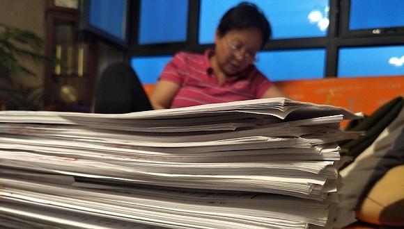 厚厚的病例和诉讼材料堆满了桌子。图片来源:刘成伟 摄